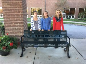 Lauren Eastman, Sydney Lindeman, and Sydney Watkins pose with a bench at Hospice of the Bluegrass that honors the service of the veterans staying there.
