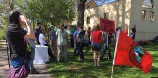 """Crowd gathered in Duncan Park. Sign in the background reads """"No War But The Class War"""""""